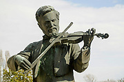 Statue of a man playing the violin on a grave in a cemetery