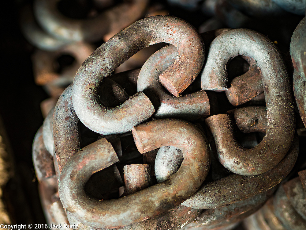 25 JANUARY 2016 - BANGKOK, THAILAND:         Finished links for a chain wait to be assembled into a chain in a small workshop in Talat Noi, Bangkok. In a small one person workshop that makes heavy chains for boat anchors. The metal for the chains is heated until it glows red and then it's pounded into shape. The Talat Noi neighborhood in Bangkok started as a blacksmith's quarter. As cars and buses replaced horse and buggy, the blacksmiths became mechanics and now the area is lined with car mechanics' and blacksmiths' shops.      PHOTO BY JACK KURTZ