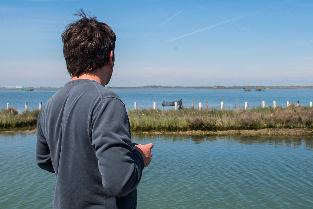 """VENICE, ITALY - APRIL 2018. <br /> A tourist enjoy the view of the Venetian lagoon while sailing along a canal close to Torcello Island during the fishing tour of the moeche. After visiting Emiliano's """"cason"""", the typical temporary house of the fishermen of the Venetian lagoon, the next stop will be in another """"cason"""", where they will taste some fresh cooked moeche."""