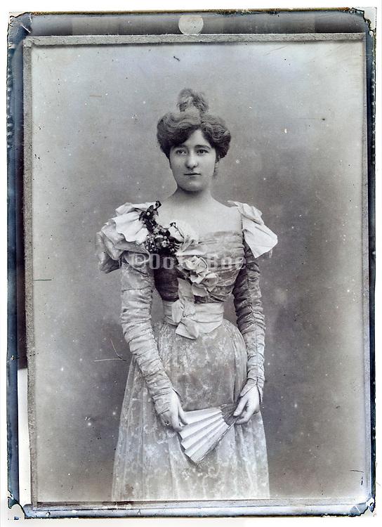 vintage studio portrait of a fashionable dressed adult woman holding a fan Paris France early 1900s