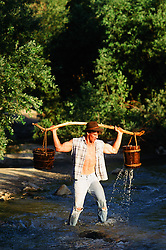 sexy man walking through a stream with two buckets and a branch over his shoulders