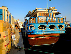 Loading cargo onto Dhows at The Creek river in Dubai United Arab Emirates UAE
