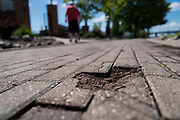 GREEN BAY, WISCONSIN - MAY 29, 2020: A view of broken bricks along the Fox River Trail in downtown Green Bay, Wisconsin on May 29, 2020. Replacing bricks along the trail is one of many public works projects that the City of Green Bay has proposed to utilize a piece the roughly $2 trillion federal stimulus package at a local level. CREDIT: Ben Brewer for the New York Times