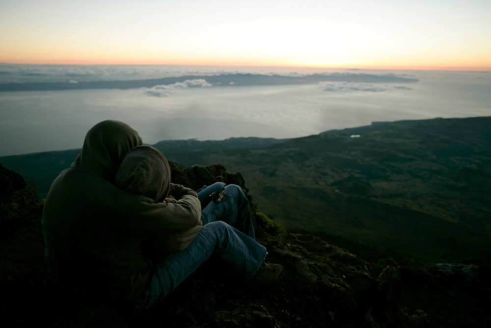 A young couple waits for dawn in the summit o Pico mountain. Sao Jorge island can be seen just in front. Pico is the highest portuguese mountain with 2351m high