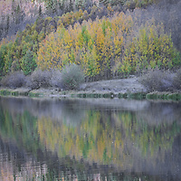 Muted autumn tones reflect beautifully on a lake in the Colorado Rockies.