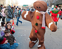The Gingerbread Man greets youngsters lining Main Street during the 2010 Laconia Holiday parade Sunday afternoon.  (Karen Bobotas/for the Laconia Daily Sun)