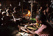Rufina Dochan and Udelia Toronam prepare a dish which Rufina claims has no name, but is made of sago grubs (Rhynchophorus ferrugineus, the larvae of Capricorn beetles), and sago flour wrapped in sago palm leaves. The packets are then roasted in the fire, Sawa Village, Irian Jaya, Indonesia. The resulting dish is like a cooked pastry, with a chewy, slightly sweet crust and the grubs taste like fishy bacon. (MEB)