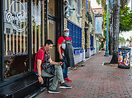 Barbers, Lino Suarez, seated, and Jorge Garcia , at right, wait outside Barberia Little Havana as they look forward to customers returning as non-essential businesses are allowed to open along Calle Ocho on Tuesday, May 19, 2020.