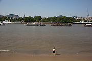 A young boy stands at the edge of the River Thames on the beach at the Southbank, London, UK. At low tide the sand is revealed and people come to play in the sand or just laze about as if on a beach. The South Bank is a significant arts and entertainment district, and home to an endless list of activities for Londoners, visitors and tourists alike.
