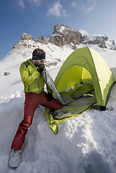 Man blowing into air mattress for camping, Tyrol, Austria