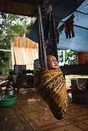 Loklahung, Indonesia - February 28, 2017: Five-month-old Regina wakes from a nap on the family's porch in a village in Loklahung, South Kalimantan, located on the island of Borneo.