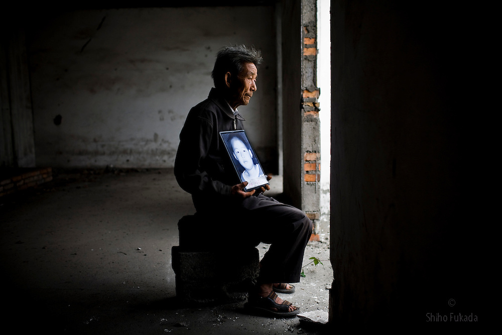 Grandfather Huang Qing Tai, 70, holding a picture of grandson Fu Hao, 11, is seen at Fuxin No.2 Primary  School in Wufu, Sichuan province.  Fu Hao's  parents work in Gongdong so he and his wife takes care of grandson.