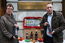 """London, UK. 3rd December, 2018. Kate Allen, Director of Amnesty UK, and Andy Slaughter, Labour MP for Hammersmith, take a Christmas hamper of """"Israeli stolen goods"""" including red wine, olive oil, honey, mineral water, eggs, dates, peppers, oranges and avocados to the Foreign Office to draw attention to the fact that these goods are all currently being produced in Israel's unlawful settlements in the occupied Palestinian West Bank and to call on governments around the world to ban the importation of Israeli settlement goods. All countries have a clear obligation to ensure respect for international humanitarian law and shouldn't recognise or assist the illegal situation that Israel's settlement policy has created."""