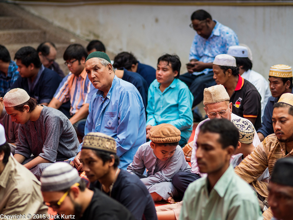 24 SEPTEMBER 2015 - BANGKOK, THAILAND: Men pray in front of the mosque during the celebration of Eid al-Adha at Haroon Mosque in Bangkok. Eid al-Adha is also called the Feast of Sacrifice, the Greater Eid or Baqar-Eid. It is the second of two religious holidays celebrated by Muslims worldwide each year. It honors the willingness of Abraham to sacrifice his son, as an act of submission to God's command. Goats, sheep and cows are sacrificed in a ritualistic manner after services in the mosque. The meat from the sacrificed animal is supposed to be divided into three parts. The family retains one third of the share; another third is given to relatives, friends and neighbors; and the remaining third is given to the poor and needy.     PHOTO BY JACK KURTZ