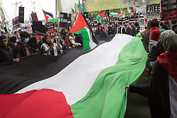 London, UK. 22nd May, 2021. Activists hold a huge Palestinian flag as tens of thousands of people take part in the National Demonstration for Palestine from Victoria Embankment to Hyde Park. It was organised by pro-Palestinian solidarity groups in protest against Israel's recent attacks on Gaza, its incursions at the Al-Aqsa mosque and its attempts to forcibly displace Palestinian families from the Sheikh Jarrah neighbourhood of East Jerusalem.