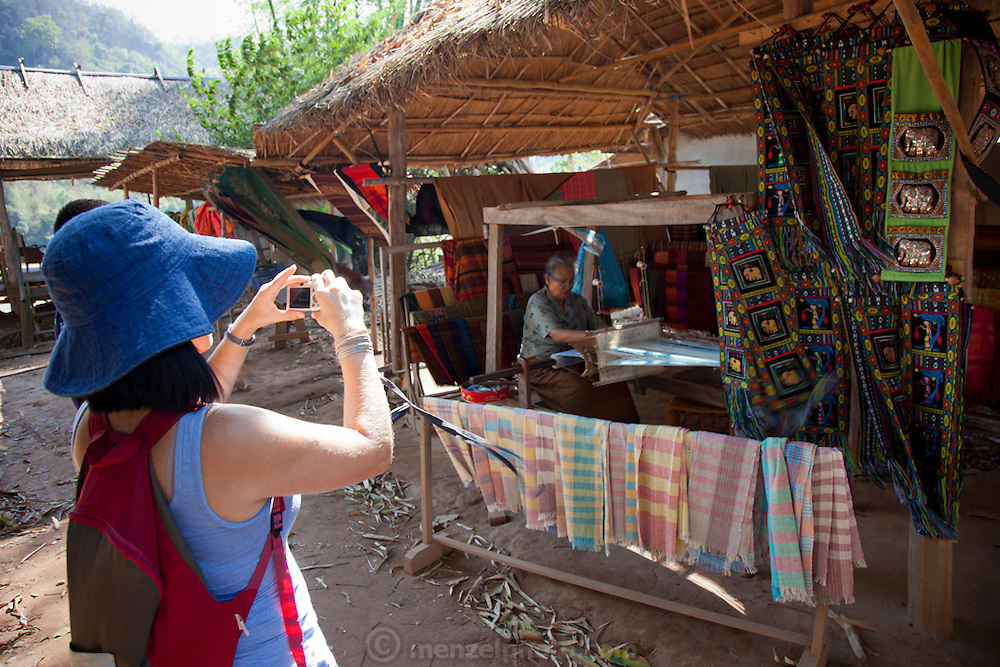 Tourist photographing a weaver in the Lao Whisky village or Ban Xang Hai village on the Mekong River near Luang Prabang. Known for potent rice wine, weaving and a small Buddhist temple in the village. A tourist stop on the way to Pak Ou (also called Tam Ting Caves)