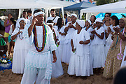 Candomble group in traditional white dress taking part in a public ceremony on the beach. February 2nd is the feast of Yemanja, a Candomble Umbanda religious celebration, where thousands of adherants visit the Rio Vermehlo Red River to make offerings of flowers and prayers, paying their respects to Yemanja, the Orixa goddess of the Sea and water.