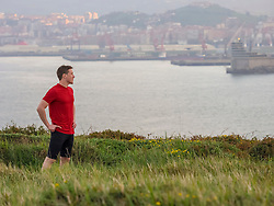 Man resting during exercise in front of port of Bilbao
