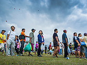 """24 JULY 2014 - BANGKOK, THAILAND: People line up for free food at the happiness party on Sanam Luang. The Thai Junta is organizing a series of public events throughout Thailand meant to bolster public opinion. The events are called """"restoring happiness to the people"""" parties. They feature historic pageants, music, food, health checks and free haircuts. The party in Bangkok is on Sanam Luang, the Royal Parade Ground, which is near the Grand Palace and the Ministry of Defense.    PHOTO BY JACK KURTZ"""