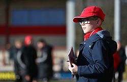 A young Fleetwood Town fan awaits autographs from the players warming up before the game