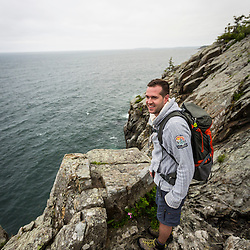 A hiker on Great Head in Maine's Acadia National Park.