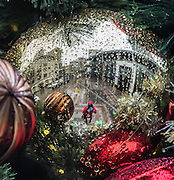 Westlake Center is reflected in the Holiday Tree balls sitting in the square showing off the rain and cold. (Steve Ringman / The Seattle Times)