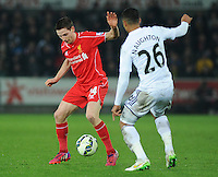 Liverpool's Joe Allen under pressure from Swansea City's Kyle Naughton<br /> <br /> Photographer Kevin Barnes/CameraSport<br /> <br /> Football - Barclays Premiership - Swansea City v Liverpool - Monday 16th March - The Liberty Stadium - Swansea<br /> <br /> © CameraSport - 43 Linden Ave. Countesthorpe. Leicester. England. LE8 5PG - Tel: +44 (0) 116 277 4147 - admin@camerasport.com - www.camerasport.com
