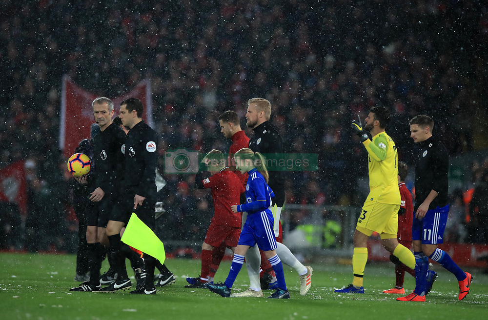 The teams walk out as snow falls during the Premier League match at Anfield, Liverpool.