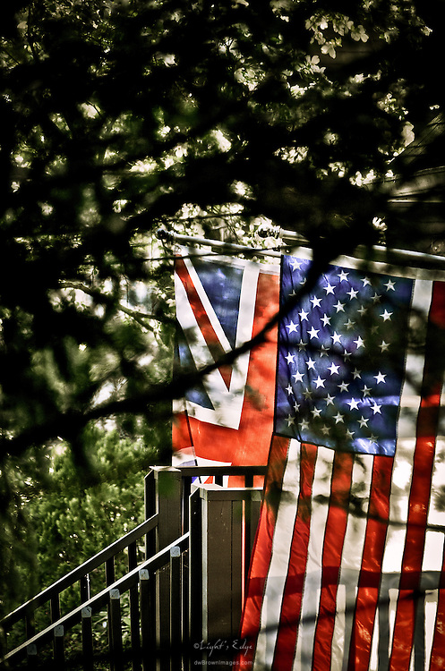 A pair of flags at the entry to a house catch the morning sun on a classic spring day.