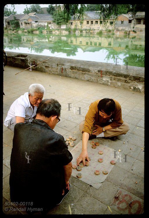 Sidewalk bordering lagoon outside Forbidden City hosts men who play a type of checkers; Beijing China