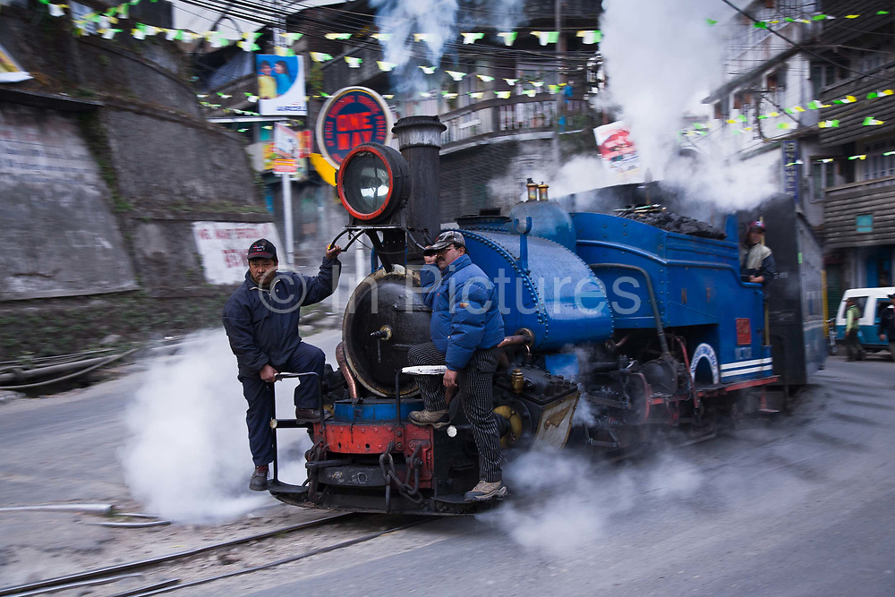 """Train driver with his assistants take the daily run from Kurseong back to Darjeeling, the shorter 32Km journey of the DHR. The Darjeeling Himalayan Railway, nicknamed the """"Toy Train"""", is a narrow-gauge railway from Siliguri to Darjeeling in West Bengal, run by the Indian Railways. It was built between 1879 and 1881 and is about 86 km long. The elevation level is from about 100 m at Siliguri to about 2200 m at Darjeeling. It is still powered by a steam engine and travels daily between the two towns.  It is now classed as a World Heritage Site by UNESCO. India."""