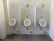 row of three urinals against a white tiled wall