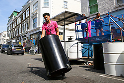 © Licensed to London News Pictures. 24/08/2019. London, UK. A man rolls a steel drum on the streets of Notting Hill, West London ahead of the 2019 Notting Hill Carnival which takes place this weekend and on bank holiday Monday. Up to 1 million people are expected to attend the biggest street party in Europe. Photo credit: Dinendra Haria/LNP