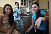 Isabella at home in the kitchen with her mother Ilana and 14 yr old sister Corinna. 19 year old Isabella Baboi at her residential home in Alexandria, where she lives with her mother and sister. She was expelled from France on 25th September by the police authorities for stealing chewing gum and face-cream. She declared herself as being homeless and returned to Romania with just the clothes she was wearing at the time of her arrest. She will return to Paris suburbs very soon, where her father and cousins are living. Alexandria, Romania..Roma Gypsies left India 1000 years ago. Often nomadic. A collection of tribes with their own languages and culture, pushed by the Ottoman empire towards Europe, used and sold as mercenaries, slaves, prostitutes. They endured 500 years of slavery until mid 19th century. A million were killed in the holocaust. Hundreds of thousands exiled and refugees from kosovo. Many Eastern Europe Roma come to the west seeking a better life. They are shunned, marginalized, excluded. Both indigenous and foriegn Roma, whether European citizens or not, lack the opportunities of others, living on the periphery, in the brunt of racism, often deported back to their countries of origin.