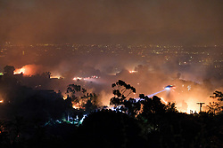 October 28, 2019, Los Angeles, California, USA: A helicopter makes a water drop on the Getty Fire in Mandeville Canyon hills in the early hours, the city lights of Los Angeles can be seen behind. The wildfire broke out on a hillside on the 405 Freeway near the Getty Center museum and has already burned several homes, forcing thousands of people to flee. (Credit Image: © David Crane/Orange County Register via ZUMA Wire)
