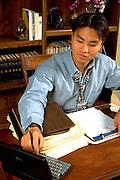 Korean businessman age 24 working on laptop computer.  St Paul Minnesota USA