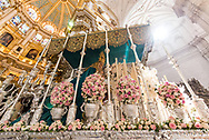 """A float """"paso"""" with a statue of the Virgin Mary stands against the lush interiors of the Cathedral of Granada at the conclusion of a procession during the Holy Week. Andalusia, Spain"""
