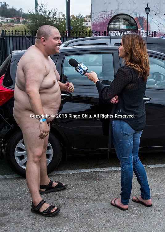 A participant is interviewed by a local TV in the World Naked Bike Ride where nude cyclists ride through Downtown Lo Angeles on June 27, 2015