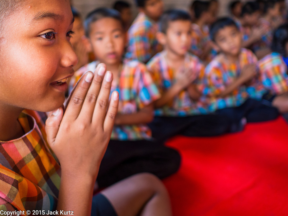 06 FEBRUARY 2015 - BANGKOK, THAILAND: Children pray after school at Wat Kalayanamitr in the Thonburi section of Bangkok is next to the Catholic community of Santa Cruz. The temple was built in 1825, about 50 years after Santa Cruz Church was built.          PHOTO BY JACK KURTZ