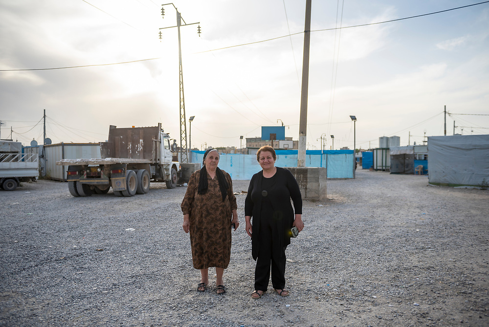 In Ankawa, a suburb of Erbil in northern Iraq, two Iraqi women pause as they walk to church in a camp for Iraqi Christians who were displaced from Qaraqosh and other towns in the Ninevah plains. Displaced by the 2014 ISIS advance, it is unclear how many will return to their original homes even after ISIS is gone.
