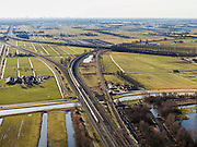 Nederland, Zuid-Holland, Gouda, 20-02-2012; Zuidplaspolder, Gouweknoop. Intercity op viaduct over het water van ringvaart van de polder. Er zijn plannen in de nu nog lege polder rechts van de bundel van spoorlijnen een nieuw station te bouwen. De intercity spoorlijn naar links naar Rotterdam, evenals rijksweg A20. Naar rechts spoorlijn naar Den Haag, Zoetermeer aan de horizon..Some railways crossing a ring canal in the polder. .luchtfoto (toeslag), aerial photo (additional fee required).copyright foto/photo Siebe Swart