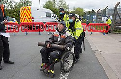 © Licensed to London News Pictures; 20/05/2021; Bristol, UK. Police move a man in a wheelchair as bailiffs evict occupants squatting on the site of a former gas works belonging to Wales and West on Glenfrome Road. The site is occupied by around 75 people including children mostly living in vehicles and caravans. Bailiffs used a crane to lift people off a scaffold tripod blocking the entrance to the site. Police led some occupants away and released them. The site was evicted last year. Photo credit: Simon Chapman/LNP.