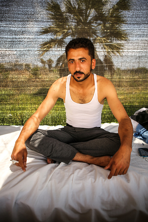 """Hassan, a 28-year-old Syrian Armed Forces defector from Al-Hasakah, poses for a portrait at the Hotel Captain Elias in Kos, Greece on June 29, 2015.<br /> <br /> """"If anyone found me, I would have been spared no mercy,"""" said Hasan through a Syrian refugee who translated from arabic to english.<br /> <br /> Hasan defected from the Syrian Armed Forces and claims that he went into hiding for 6 months from the Kurdish Workers' Party (PKK) and other rebel groups in Al-Hasakah, the capital city of the Al-Hasakah Governorate located in the far north-eastern corner of Syria. He left his wife and 2-year-old son in Syria after fleeing to the greek island of Kos.<br /> <br /> """"I was imprisoned for 2 days by the PKK after intelligence and civil service went to my home searching for me…I escaped and left Syria,"""" Hasan said.<br /> <br /> Hasan paid $200 USD to illegally cross the Turkish border after 3 failed attempts. He ran for about 3 kilometers after crossing the Turkish border at night until he reached a safe space. He spent the night of his arrival in a Turkish mosque with no one around. The morning after, Hasan took a bus directly to Bodrum, Turkey where he stayed in a hotel with a smuggler for 5 days. Hasan attempted going to Greece everyday, but failed until the fifth day.<br /> <br /> """"I paid $1,100 to go from Bodrum to Kos,"""" said Hasan. """"The smuggler promised me a safety jacket, but I never got one. The smuggler also promised he would bring me my bag with all my things and forgot it. He lied to me,"""" said Hassan.<br /> <br /> Hasan arrived to the island of Kos in a boat carrying about 30 people, 4 of them from Syria and the rest from Afghanistan.<br /> <br /> """"From Bodrum to Kos, I prayed all the way. I was so afraid,"""" said Hasan."""