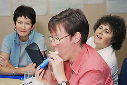 Women blowing into device to monitor carbon monoxide levels during antismoking training session,
