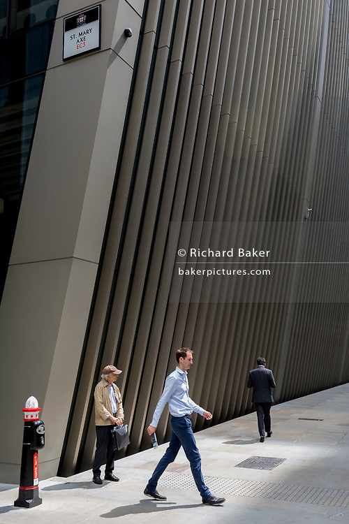 Three man on the corner of Bevis Marks and St. Mary Axe in the City of London, the capital's financial district (aka the Square Mile), on 10th July 2019, in London England.