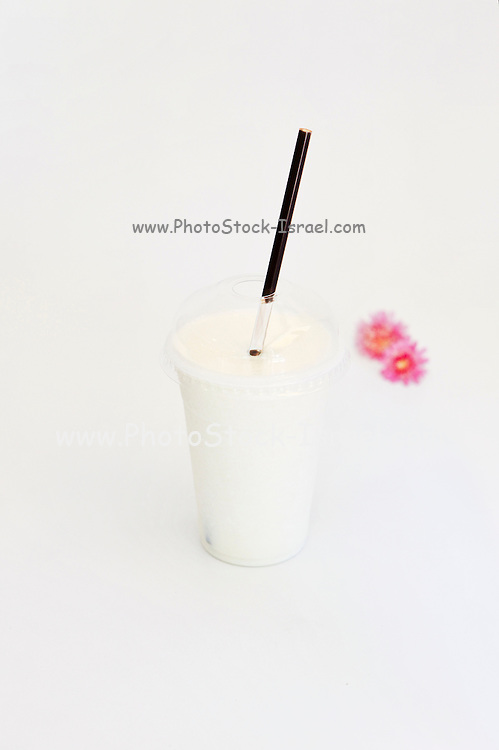 Vanilla flavoured smoothie in disposable cup on white