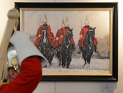 "© Licensed to London News Pictures. 20/04/2012. London, UK . A soldier adjusts his helmet in front of ""Queen's Life Guard in the Snow"" by Katie Scorgie. A Preview of the Household Cavalrys 'The Best of British' art exhibition. Soldiers walk around the artwork as they prepare to mount duties at Horse Guards Parade. The Queen's Life Guard are inspected before they depart the Barracks for the daily Guard change at 1100. The exhibition runs between 23 - 26 April. Hyde Park Barracks, Ceremonial Gate, South Carriage Drive, London, SW7 1SE. Photo credit : Stephen Simpson/LNP"
