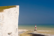 Beachy Head lighthouse next to the seven sisters chalk cliffs. 2 people walking along the top. Since April 2011 part of South Downs National Park.