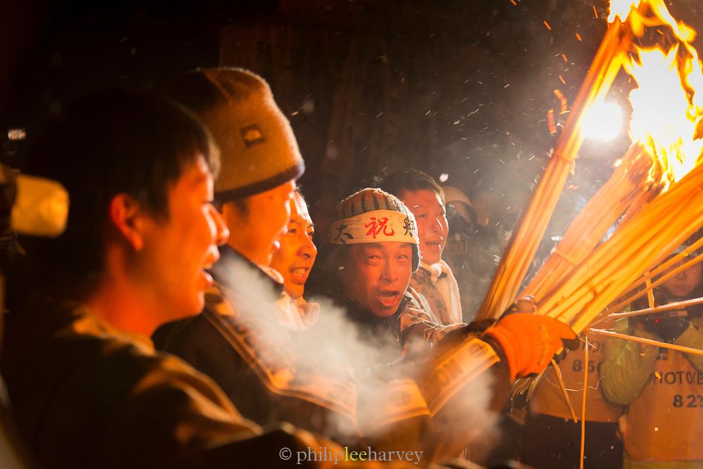Group of people holding burning straw at night, Nozawaonsen, Japan