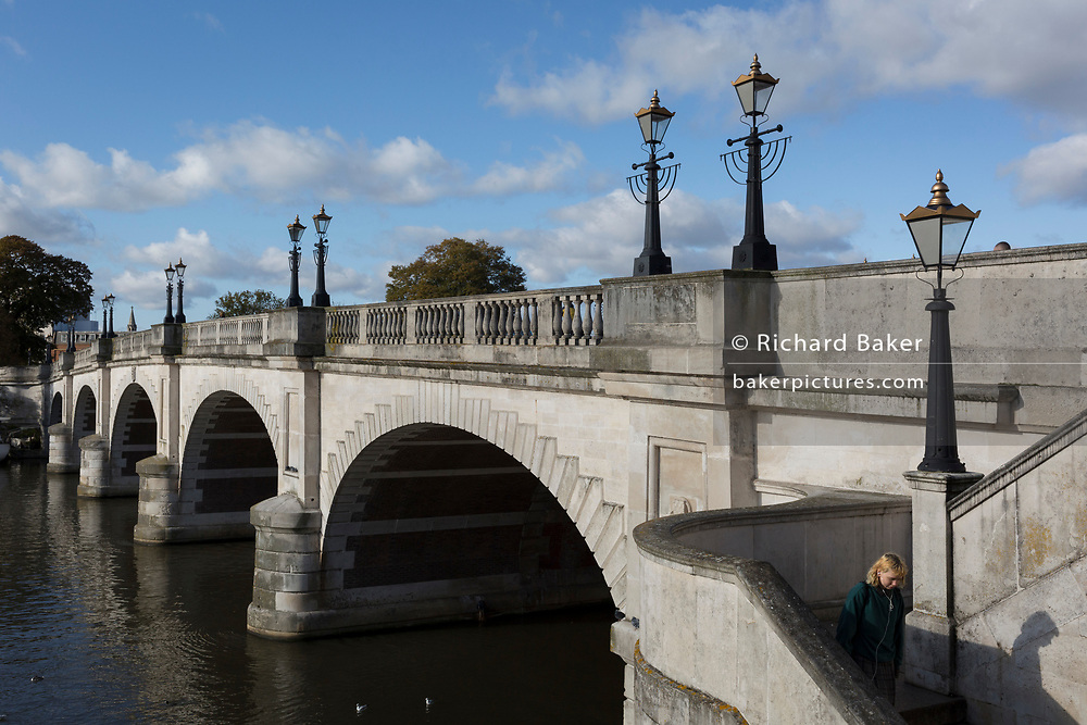 Seen from the southern bank of the river Thames is the architecture of Kingston Bridge where a pedestrian stops to take a selfie photo, on 7th November 2019, in Kingston, London, England. A crossing has existed at Kingston since ancient times and this version of Kingston Bridge was constructed by Herbert for £26,800 and opened by the Duchess of Clarence (the future Queen Adelaide) on 17 July 1828. Constructed from Portland stone, it comprises of five elliptical arches.